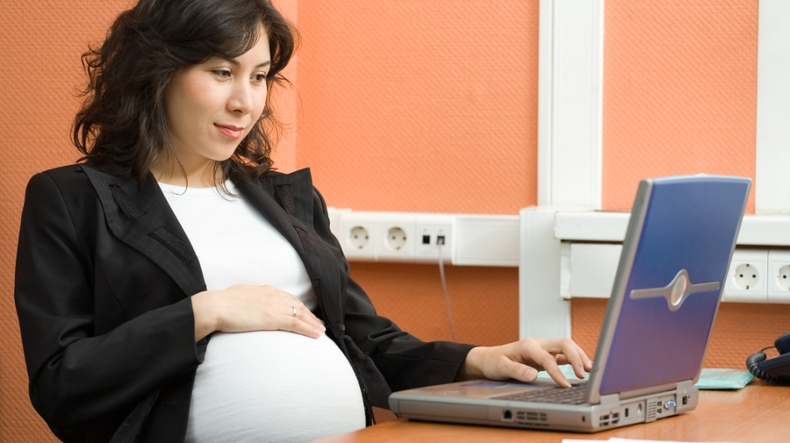 A pregnant woman working in the office