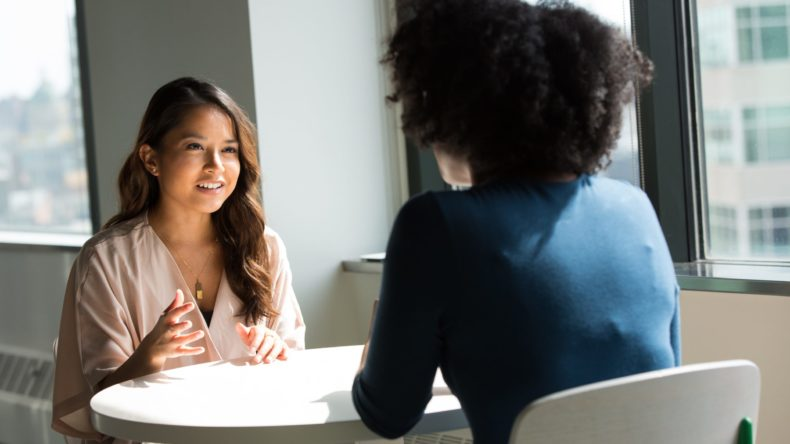 women speaking with each other in office