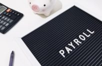 payroll with calculator and piggy bank