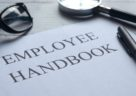 employee handbook with pen and magnifying glass