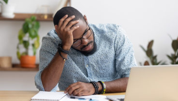 Tired depressed bored african businessman frustrated by business failure